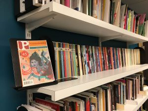 "45th anniversary issue of ""Ploughshares"" on a bookshelf full of ""Ploughshares"" magazines"