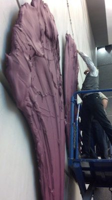 Man on lift hanging one of Donald Martiny's pieces: a purple sculpture/painting of a brushstroke