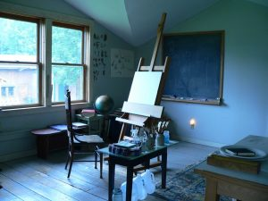 A studio, with an easel in the middle eand chalkboard on the wall