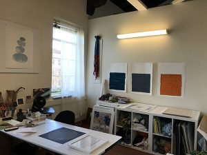 A photograph of a textile artist's studio with work hanging from the walls
