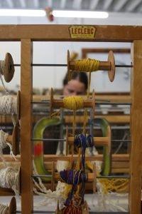 A photograph of artist Britta Fluevog working at her loom