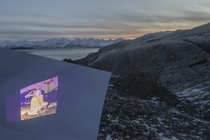 A photograph of a projection overlooking a shoreline